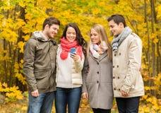 Amis de sourire avec des smartphones en parc de ville Image libre de droits