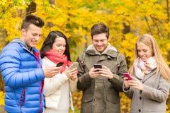 Amis de sourire avec des smartphones en parc de ville Photo libre de droits