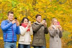 Amis de sourire avec des smartphones en parc de ville Photographie stock libre de droits