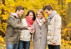Amis de sourire avec des smartphones en parc de ville Image stock