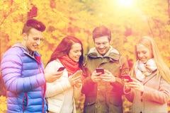 Amis de sourire avec des smartphones en parc de ville Photographie stock