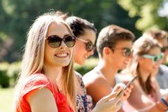 Amis de sourire avec des smartphones se reposant en parc Photos libres de droits