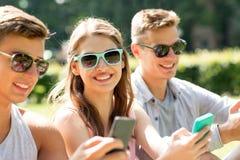 Amis de sourire avec des smartphones se reposant en parc Photographie stock libre de droits