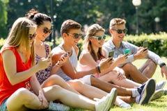 Amis de sourire avec des smartphones se reposant sur l'herbe Image stock