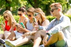 Amis de sourire avec des smartphones se reposant sur l'herbe Images libres de droits