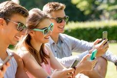 Amis de sourire avec des smartphones se reposant sur l'herbe Photos stock