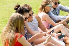 Amis de sourire avec des smartphones se reposant sur l'herbe Images stock