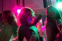 Amis de sourire avec des verres de champagne dans le club Photographie stock libre de droits