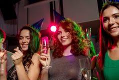 Amis de sourire avec des verres de champagne dans le club Image stock