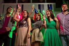 Amis de sourire avec des verres de champagne dans le club Photos stock