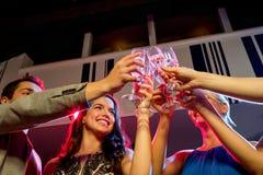 Amis de sourire avec des verres de champagne dans le club Photographie stock