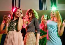 Amis de sourire avec des verres de champagne dans le club Images stock