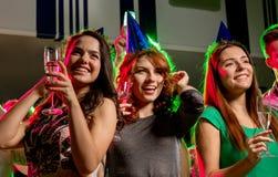 Amis de sourire avec des verres de champagne dans le club Photo libre de droits