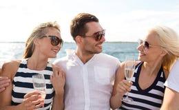 Amis de sourire avec des verres de champagne sur le yacht Photo libre de droits