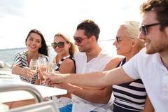 Amis de sourire avec des verres de champagne sur le yacht Image libre de droits