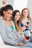 Amis de sourire avec des verres de vin à la maison Images libres de droits
