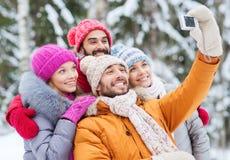 Amis de sourire avec l'appareil-photo dans la forêt d'hiver Images stock