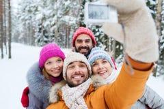 Amis de sourire avec l'appareil-photo dans la forêt d'hiver Photographie stock