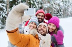 Amis de sourire avec l'appareil-photo dans la forêt d'hiver Image stock