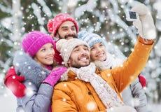 Amis de sourire avec l'appareil-photo dans la forêt d'hiver Photo stock
