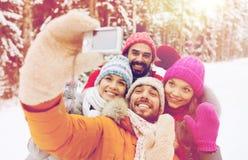 Amis de sourire avec l'appareil-photo dans la forêt d'hiver Images libres de droits