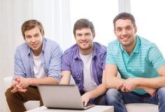 Amis de sourire avec l'ordinateur portable à la maison Images stock