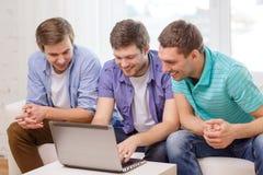Amis de sourire avec l'ordinateur portable à la maison Photo libre de droits