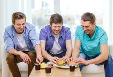 Amis de sourire avec la soude et les hamburgers à la maison Photo stock