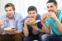 Amis de sourire avec la soude et les hamburgers à la maison Photo libre de droits