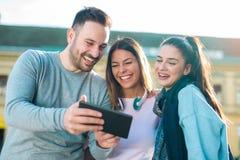 Amis de sourire avec le comprimé numérique extérieur Photos stock