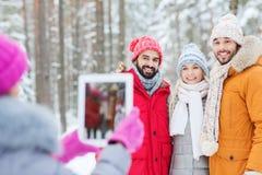 Amis de sourire avec le PC de comprimé dans la forêt d'hiver Photo libre de droits