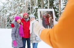 Amis de sourire avec le PC de comprimé dans la forêt d'hiver Photos stock
