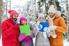 Amis de sourire avec le PC de comprimé dans la forêt d'hiver Photos libres de droits