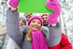 Amis de sourire avec le PC de comprimé dans la forêt d'hiver Images stock