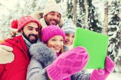 Amis de sourire avec le PC de comprimé dans la forêt d'hiver Image libre de droits