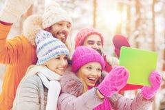 Amis de sourire avec le PC de comprimé dans la forêt d'hiver Photo stock