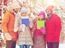 Amis de sourire avec le PC de comprimé dans la forêt d'hiver Image stock