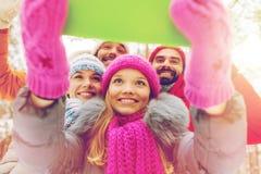 Amis de sourire avec le PC de comprimé dans la forêt d'hiver Photographie stock libre de droits