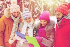 Amis de sourire avec le PC de comprimé dans la forêt d'hiver Photographie stock