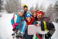 Amis de sourire avec le ski des vacances d'hiver - skieurs ayant l'amusement Photographie stock