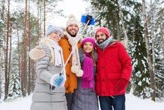 Amis de sourire avec le smartphone dans la forêt d'hiver Images stock