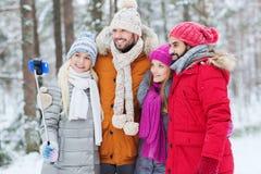 Amis de sourire avec le smartphone dans la forêt d'hiver Images libres de droits