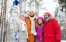 Amis de sourire avec le smartphone dans la forêt d'hiver Photos stock