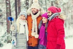 Amis de sourire avec le smartphone dans la forêt d'hiver Photo libre de droits