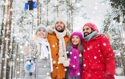 Amis de sourire avec le smartphone dans la forêt d'hiver Photographie stock libre de droits