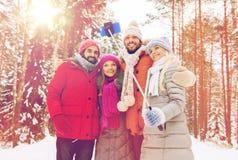 Amis de sourire avec le smartphone dans la forêt d'hiver Photo stock