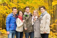 Amis de sourire avec le smartphone en parc de ville Photo stock