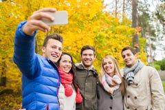Amis de sourire avec le smartphone en parc de ville Images stock