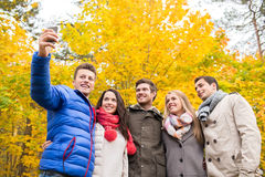 Amis de sourire avec le smartphone en parc de ville Images libres de droits