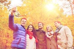 Amis de sourire avec le smartphone en parc de ville Photos stock